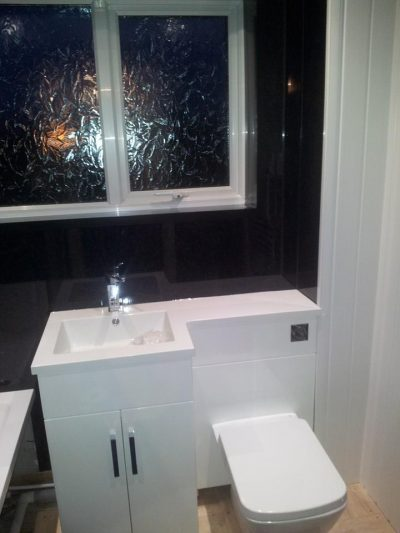 modern sink unit in black tiled bathroom
